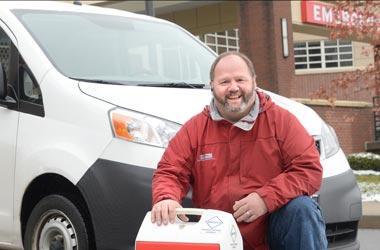 Blog James Rivers kneeling by van in front of Saratoga Hospital