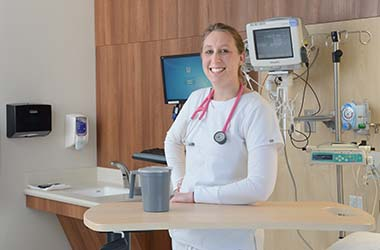 Kayleigh Eschler standing in hospital room