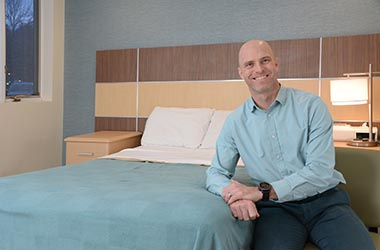 Kenneth Plowman leaning against clinic bed