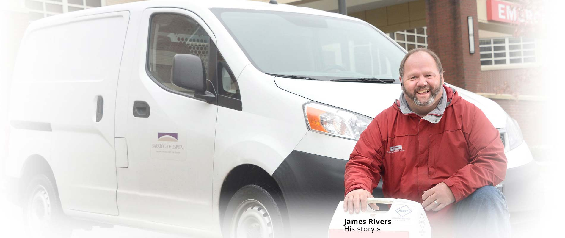 James Rivers kneeling by van in front of Saratoga Hospital